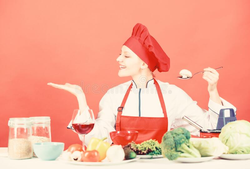 Cooking meal. Woman chef try taste eat food. Delicious recipe concept. Girl at kitchen table. Cooking food and stock images