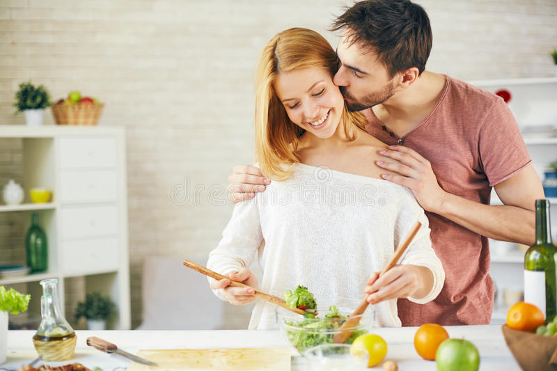 Cooking moment. Affectionate young men kissing his wife while she cooking salad stock image