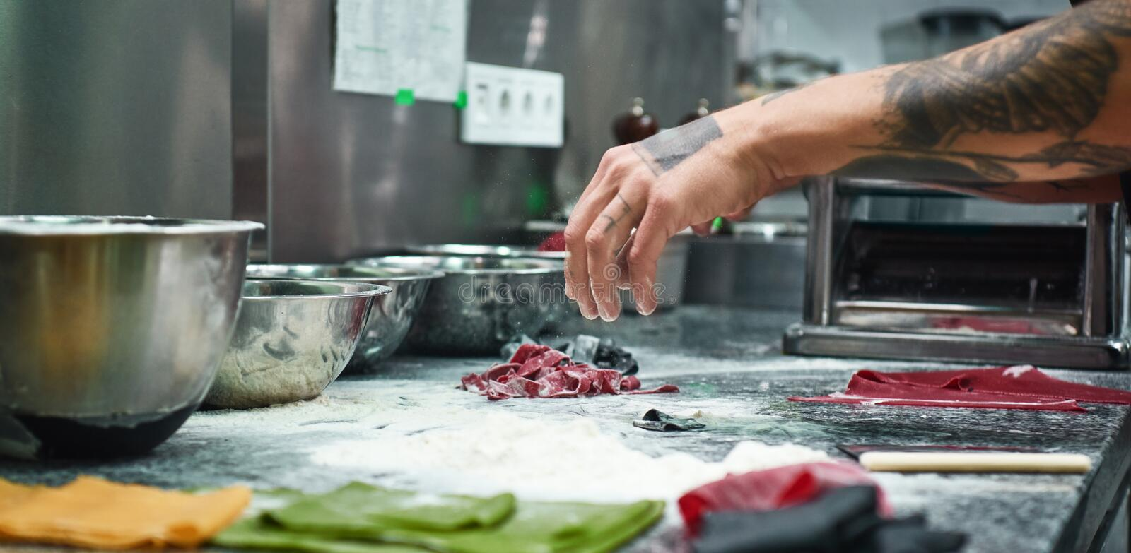 Cooking moments. Cropped image of chef`s hands with beautiful tattoos making traditional italian pasta in restaurant royalty free stock photos