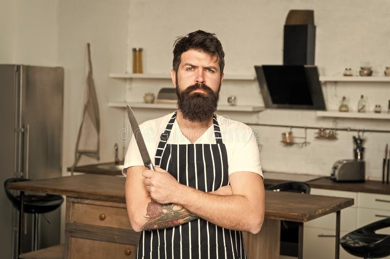 Cooking is my passion. brutal man in cook apron with sharp knife. mature male with beard cooking. culinary business royalty free stock photography