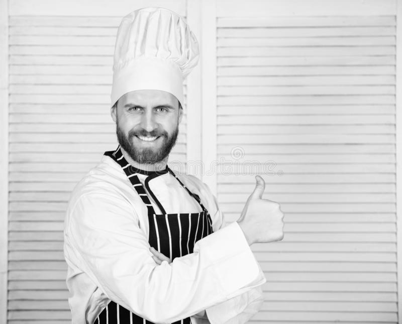 Cooking is my passion. Professional in kitchen. culinary cuisine. cook in restaurant. chef ready for cooking. confident. Man in apron and hat hold thumb up royalty free stock photography