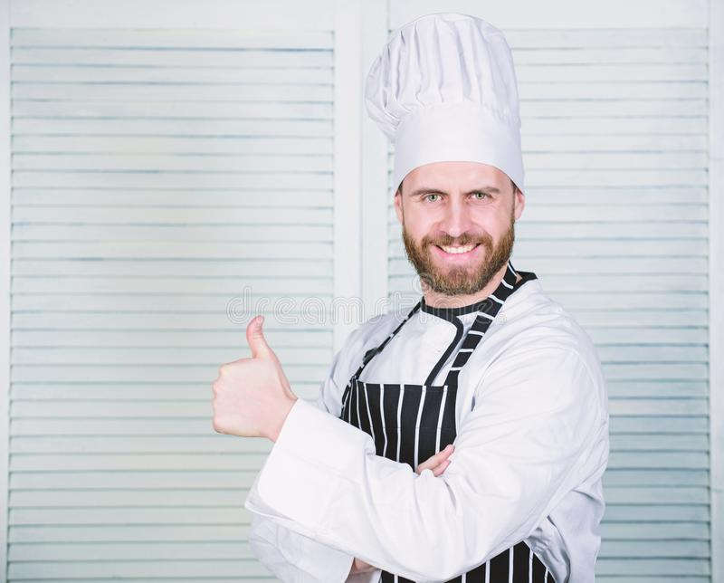 Cooking is my passion. Professional in kitchen. culinary cuisine. cook in restaurant. chef ready for cooking. confident. Man in apron and hat hold thumb up stock photography
