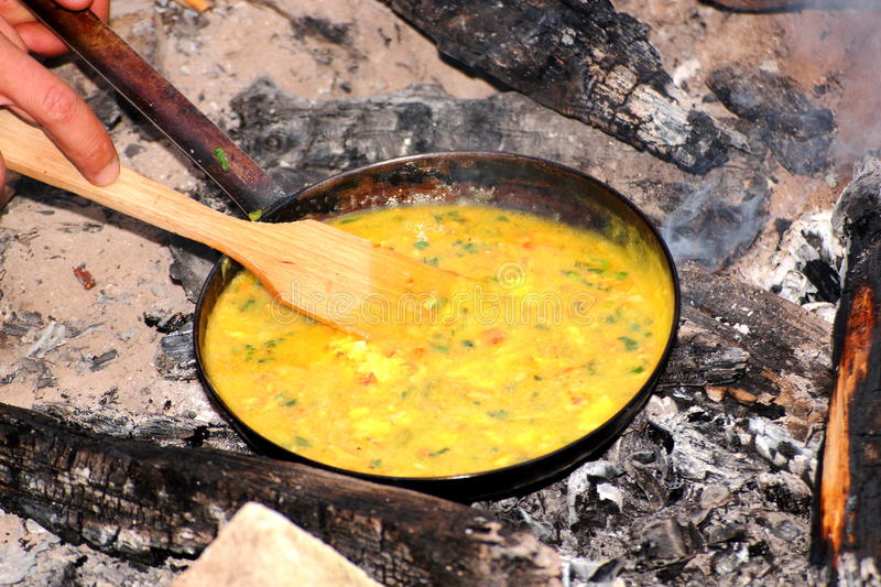 Cooking omelette on camp fire stock images