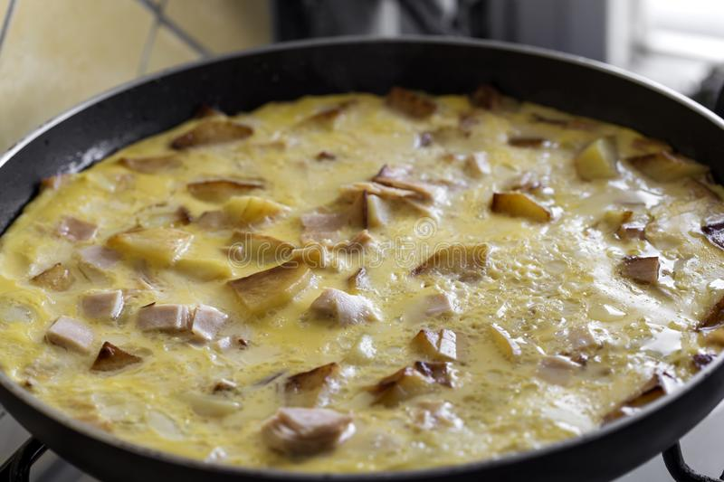 Cooking omelette made with eggs, potatoes and ham stock photography
