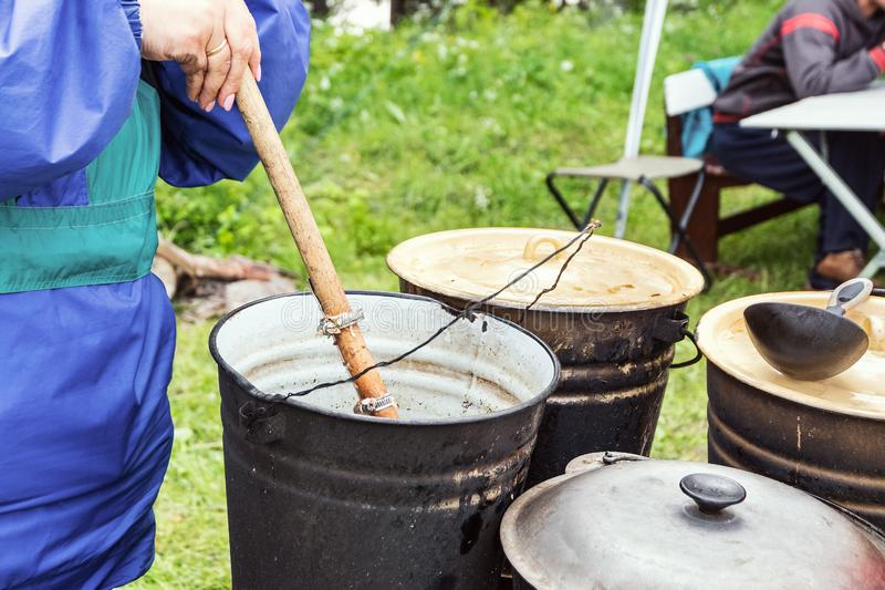 Cooking outdoors. Charity. Distribution of food to hungry people stock image