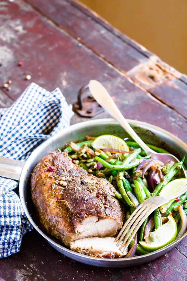 Cooking pan of gourmet meal. Roasted pork loin with spices served with warm salad made from green beans, onion, lime fruit on a wo royalty free stock image
