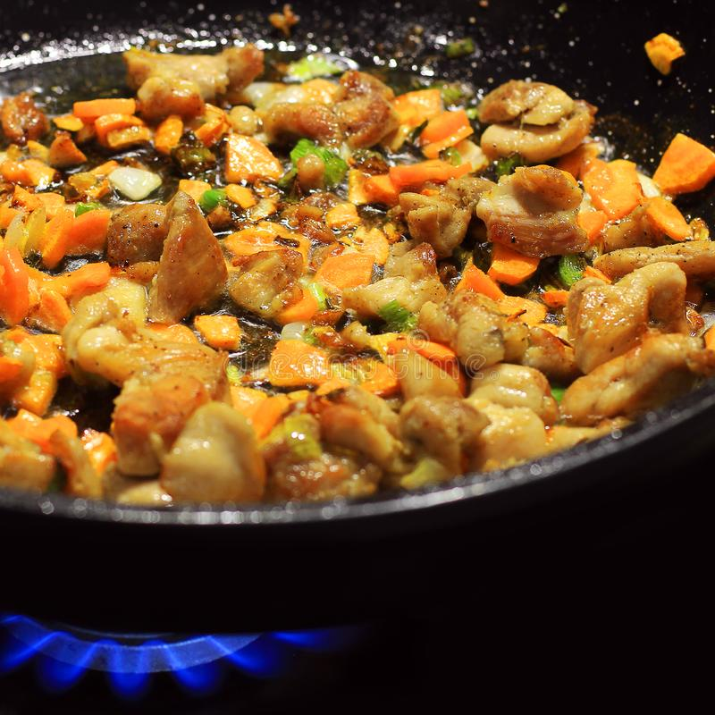 Cooking in a pan. Roasted meat and vegetables stock images