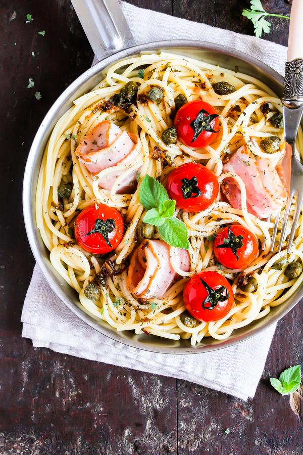 Cooking pan with traditional italian pasta spaghetti with roasted cherry tomatoes, capers and bacon with mint on a wooden table, s royalty free stock image