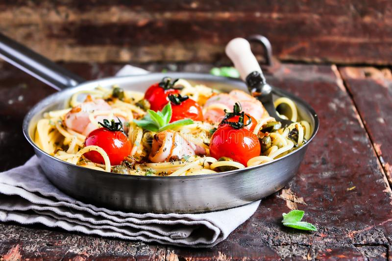 Cooking pan with traditional italian pasta spaghetti with roasted cherry tomatoes, capers and bacon with mint on a wooden table, s stock photo