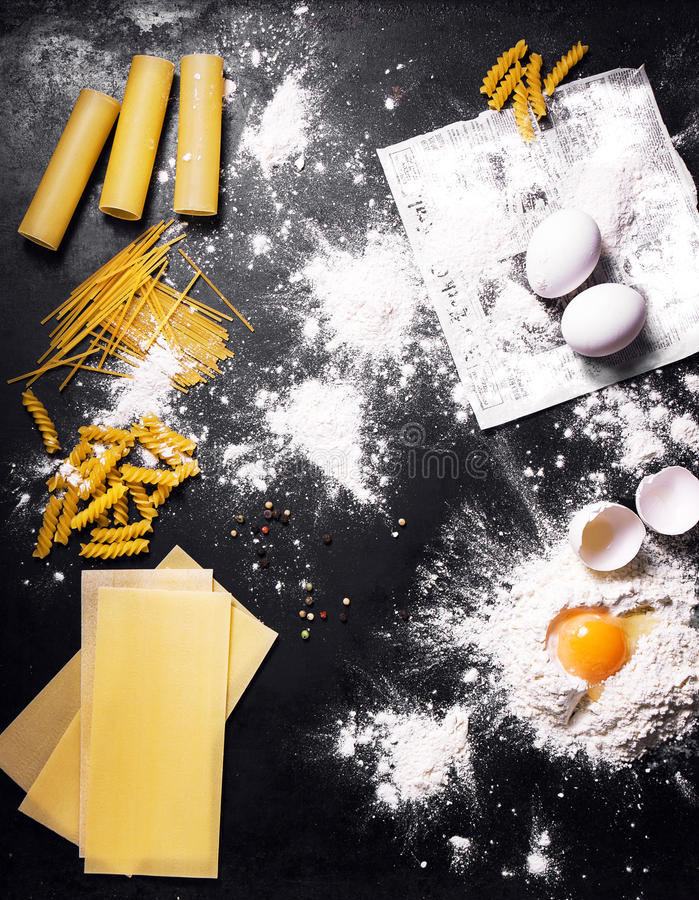 Cooking pasta concept: top view or view from above with ingredients for pasta on a dark background royalty free stock photos