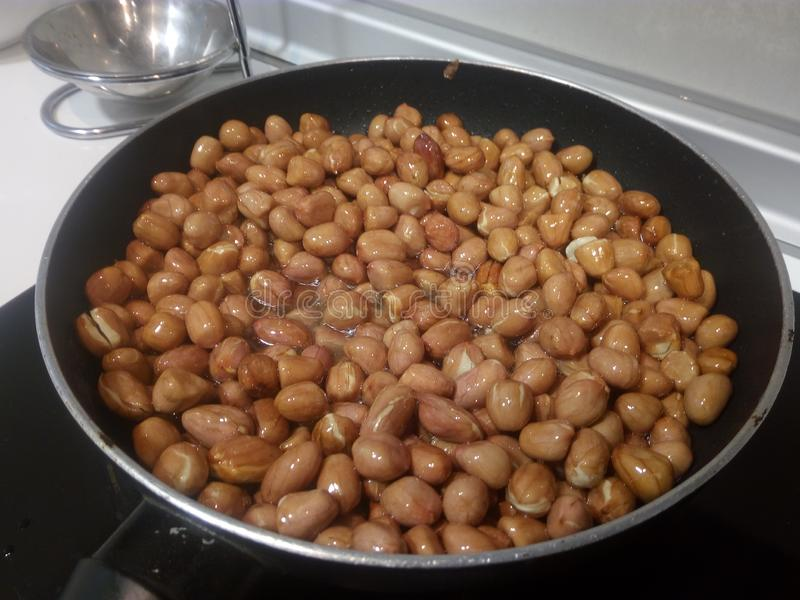 Cooking peanuts in a frying pan. Cooking peanuts frying pan  kitchen oil oliveoil food diet appetizer sane fried taste homemade royalty free stock photos