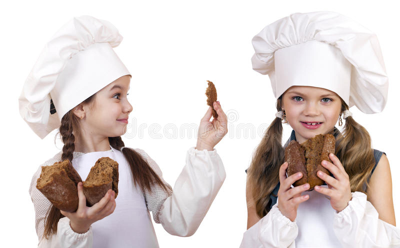 Cooking and people concept - Two little girls in cook hat. Cooking and Children concept - Two smiling little girls in cook hat, isolated on white background royalty free stock photos