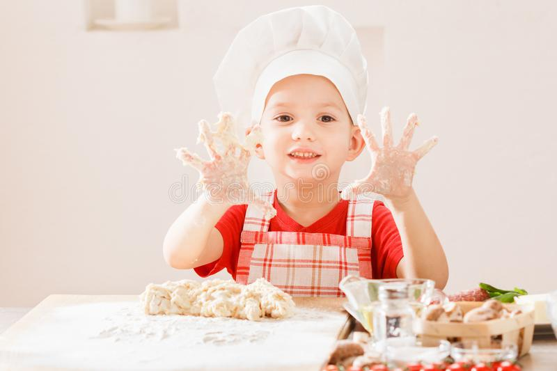 Cooking pizza is fun - little chef playing with flour. Making the dough for pizza is fun - little chef playing with flour royalty free stock image