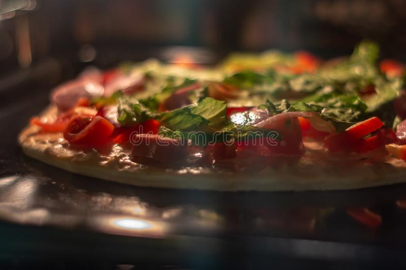 Cooking pizza in hot air oven, soft focus stock photo
