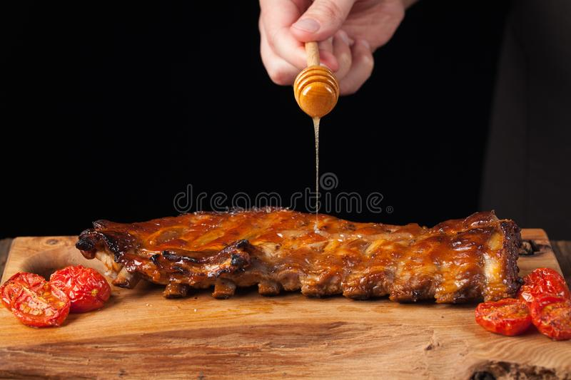 Cooking pork rib chops with honey sweet sauce on dark wooden background. The chef pours honey pork ribs. With copy space royalty free stock photo