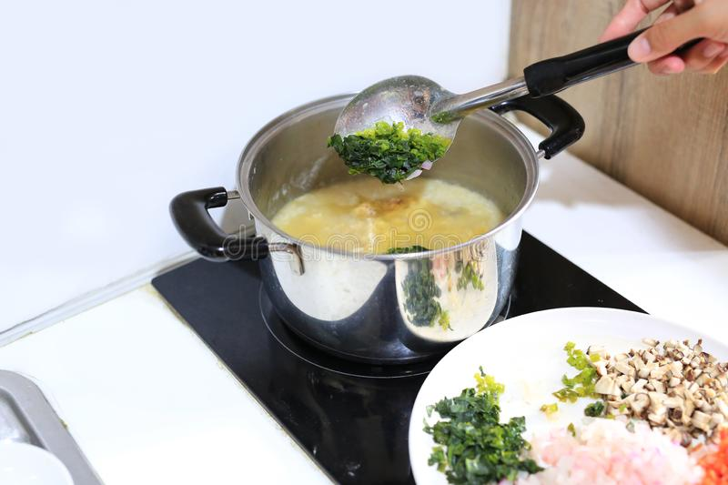 Cooking Porridge for baby food in pot on electric stove royalty free stock photos