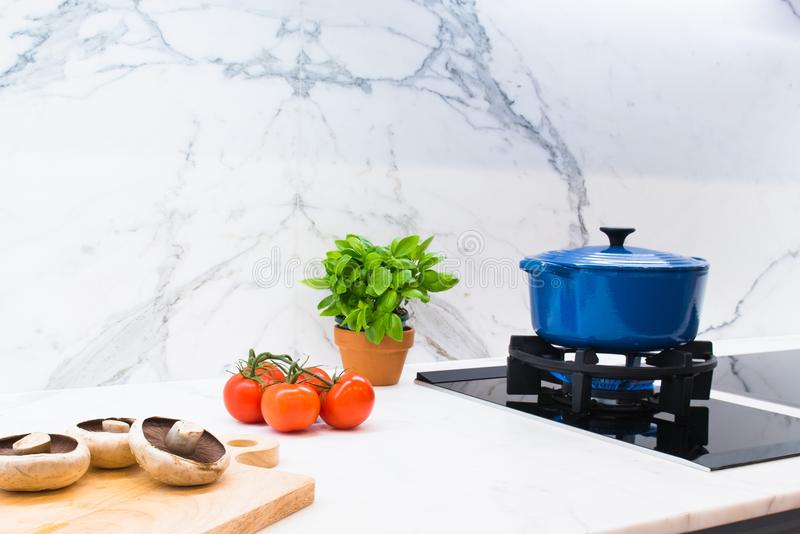 Cooking pot and ingredients on marble kitchen bench stock photo