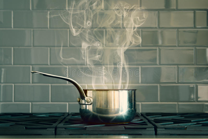 Cooking Pot With Smoke On A Grey Bricked Background stock photos