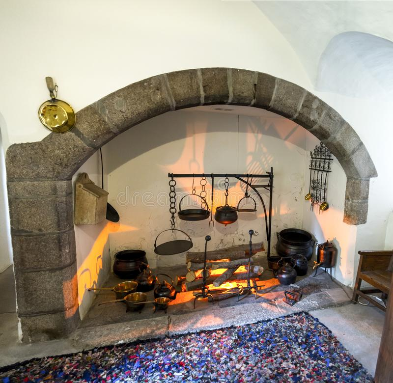 Cooking pots in a decorative lighted fireplace in one of the room of Crathes Castle. Aberdeenshire, Scotland royalty free stock image