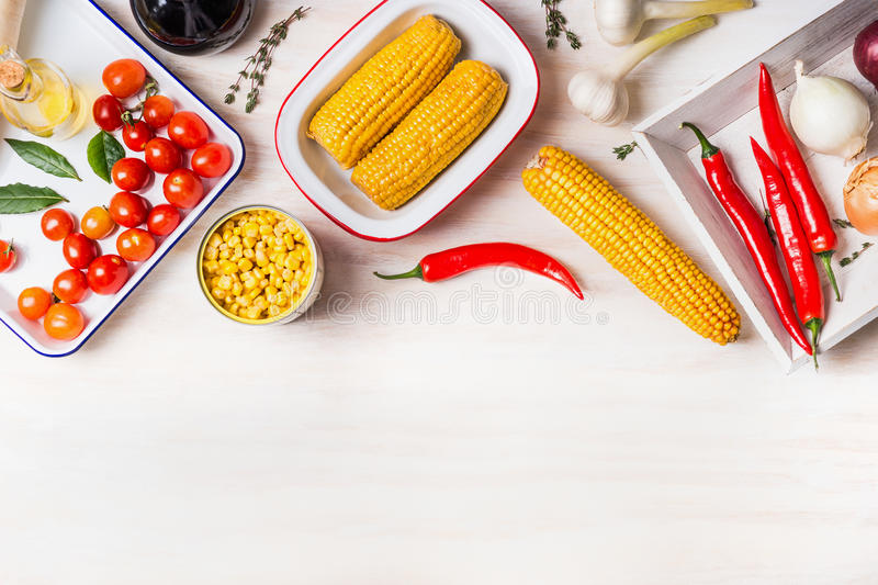 Cooking preparation with ear of corn, canned and cooked corn and ingredients for vegetarian dish on white wooden kitchen table ba stock photography