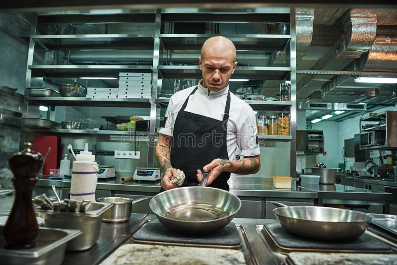 Cooking process. Brutal male chef with several tattoos on his arms holding a frying pan with oil above the oven in a stock photo