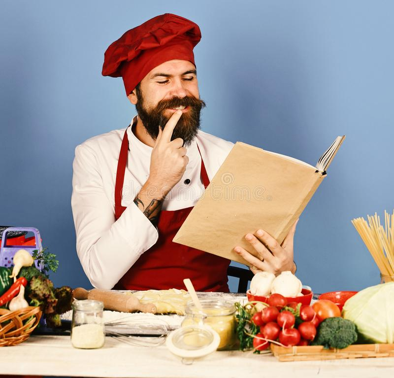Cooking process concept. Man with beard holds recipe book. Or menu on blue background. Cook with happy face in burgundy uniform reads cook book having idea stock images