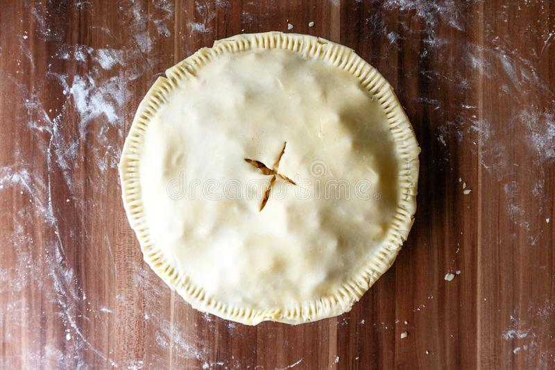 Cooking process. Indoor American apple pie with shortcrust pastry on a dark wooden background. Rolled raw dough. View from above. stock images