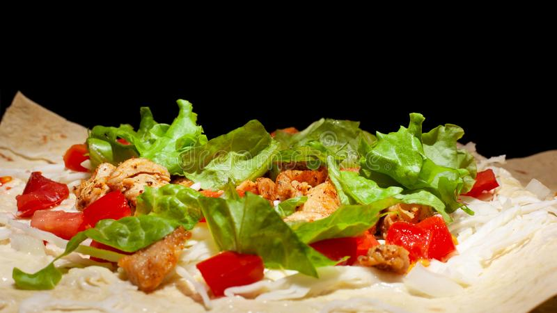 Cooking process pita sandwich with fresh vegetables,Concept: healthy food on a dark background royalty free stock photos