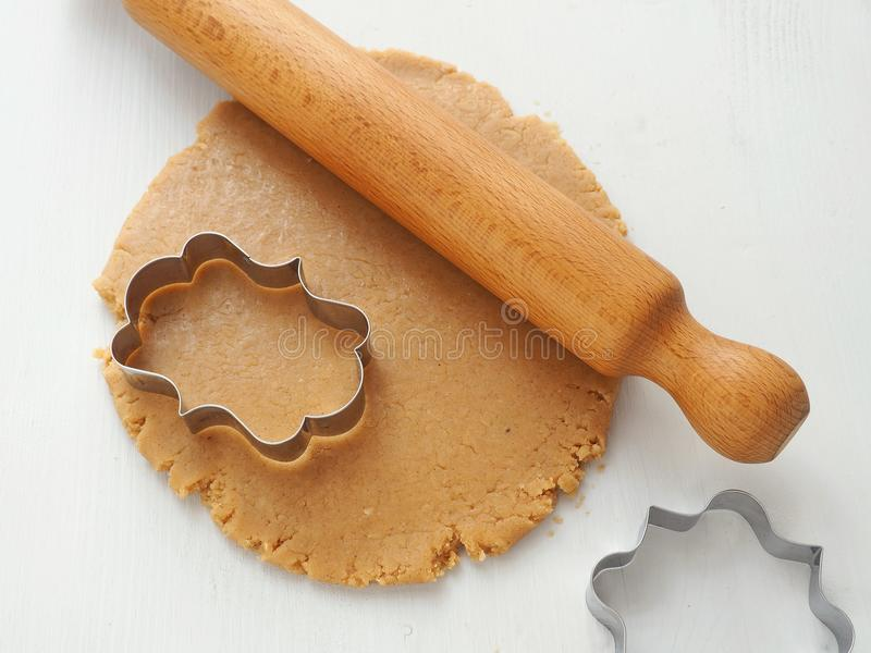 Cooking process. Rolled up dough for gingerbread, cookies, shortbread, pastries upon white wooden table. royalty free stock image