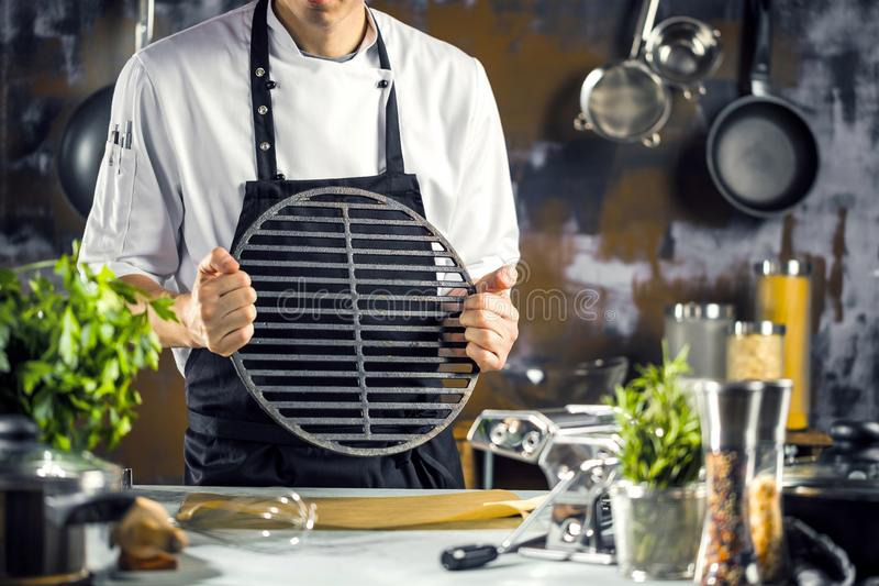 Cooking, profession and people concept - male chef cook making food at restaurant kitchen royalty free stock photography