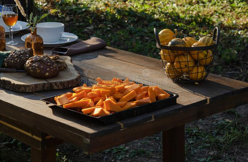 Cooking pumpkin pie, soup and table setting in the garden on the background of homemade bread with  seeds and decorative pu stock photos