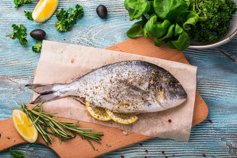 Cooking Raw Dorado Fish with Spinach, rosemary, olives, Herbs, Spices and Lemon closeup on Wooden Cutting Board on an aquamarine b royalty free stock photography