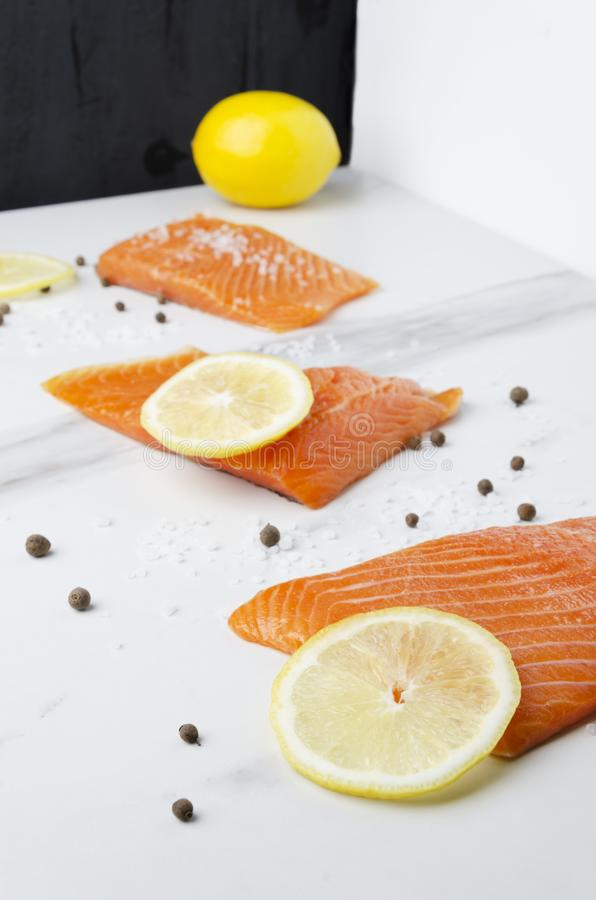 Cooking of raw tasty salmon with yellow lemon and pepper in the kitchen royalty free stock photo