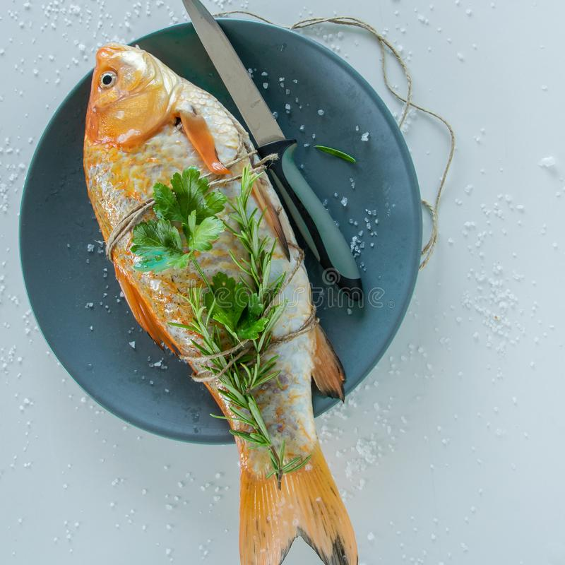 Cooking red  Carassius fish with fresh herbs. Healthy eating concept, space for text stock images