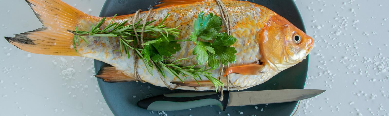 Cooking red  Carassius fish with fresh herbs. Healthy eating concept, space for text stock photography