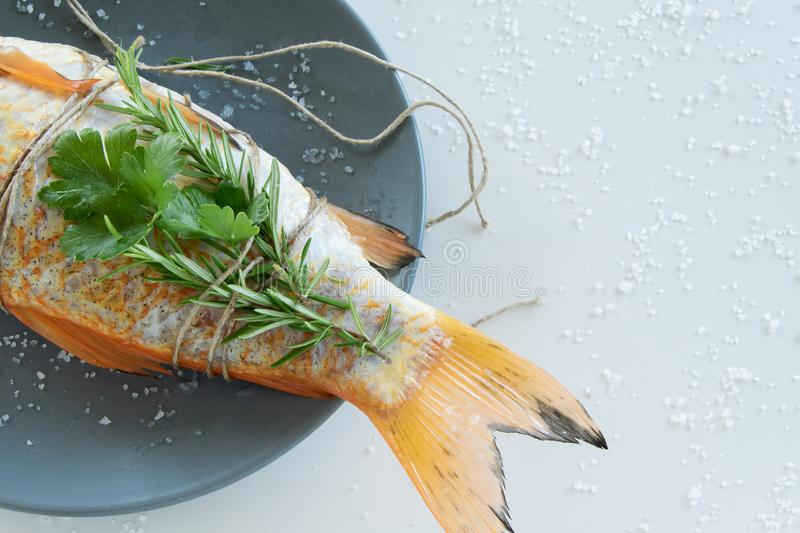 Cooking red  Carassius fish with fresh herbs. Healthy eating concept, space for text stock photos