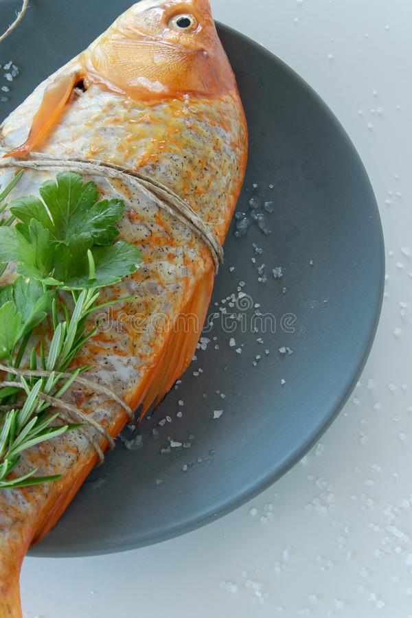 Cooking red  Carassius fish with fresh herbs. Healthy eating concept, space for text royalty free stock photos