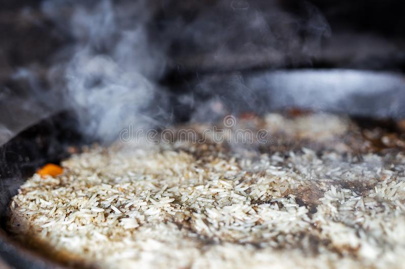 Cooking Rice for pilaw or paella in iron cauldron over open fire. Smoke and steam. Tasty food preparing outdoor process. Background stock photos