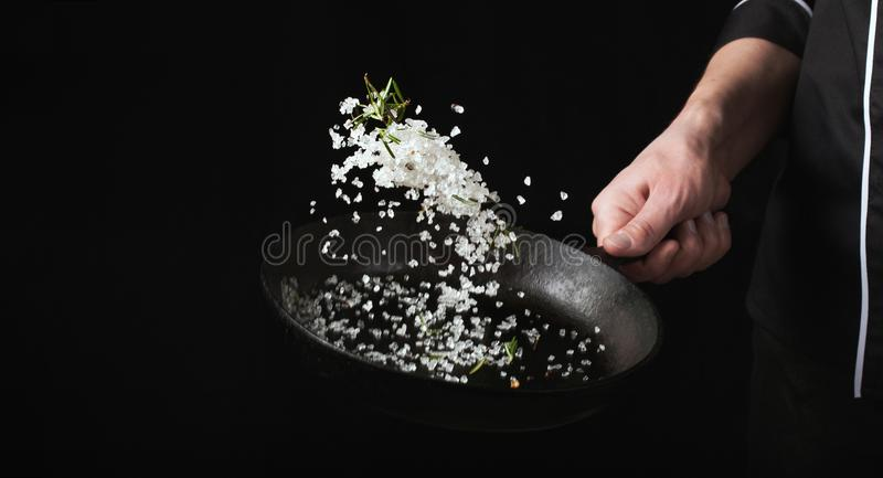 Cooking roasted aromatic salt in a pan by chef hand. Horizontal photo view. Dark black background with copy text area royalty free stock photos