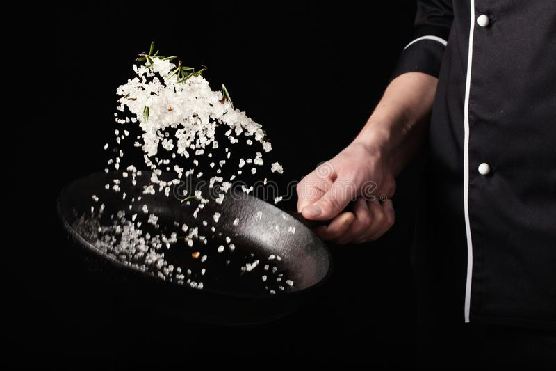 Cooking roasted aromatic salt in a pan by chef hand. Horizontal photo view. Dark black background with copy text area stock images