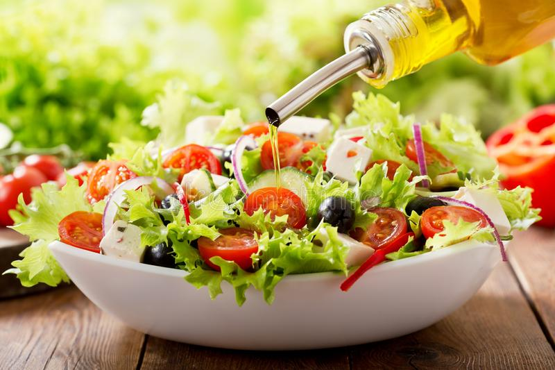 Cooking salad. olive oil pouring into bowl of fresh salad stock image