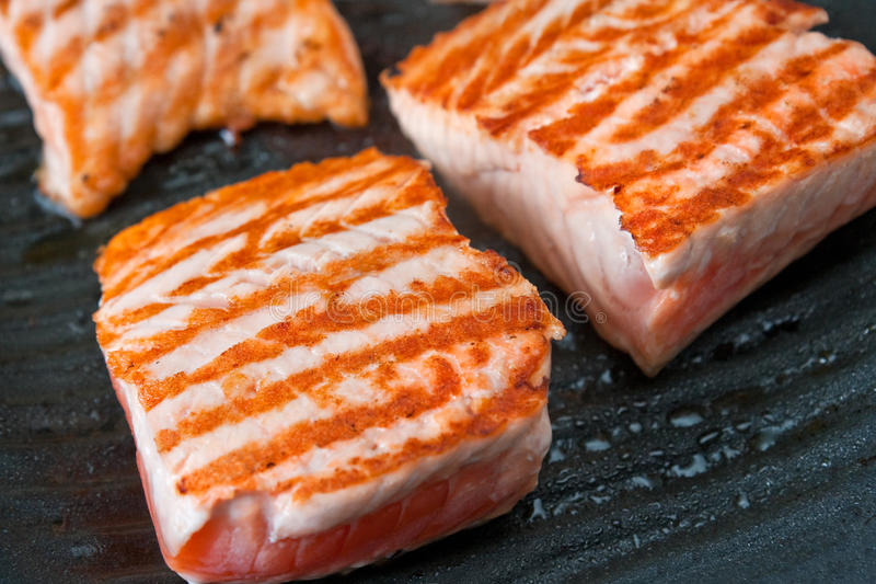 Cooking salmon steak on the grill royalty free stock photo