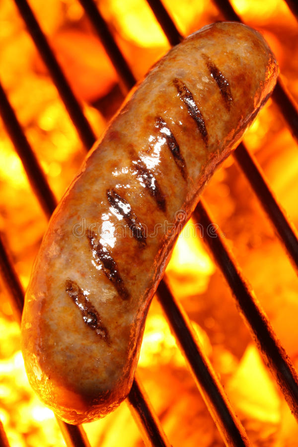 Cooking a sausage hot dog on barbecue grill. Sausage or hot dog on a fire hot barbecue grill. Barbecue & Outdoor Cooking Collection stock photo
