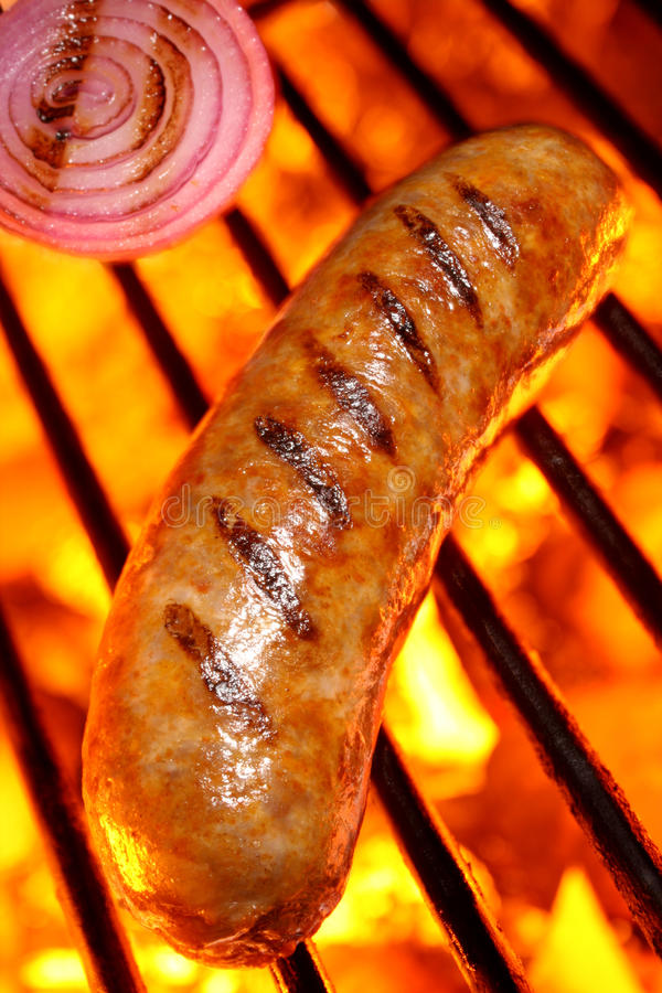Cooking a sausage hot dog on barbecue grill. Sausage or hot dog on a fire hot barbecue grill. Barbecue & Outdoor Cooking Collection stock images