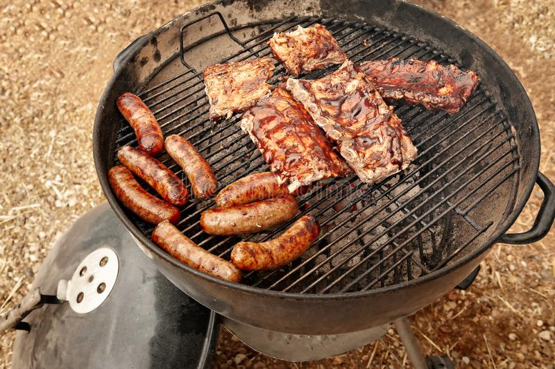Cooking sausages and racks of ribs outdoors on a charcoal fueled grill. stock images