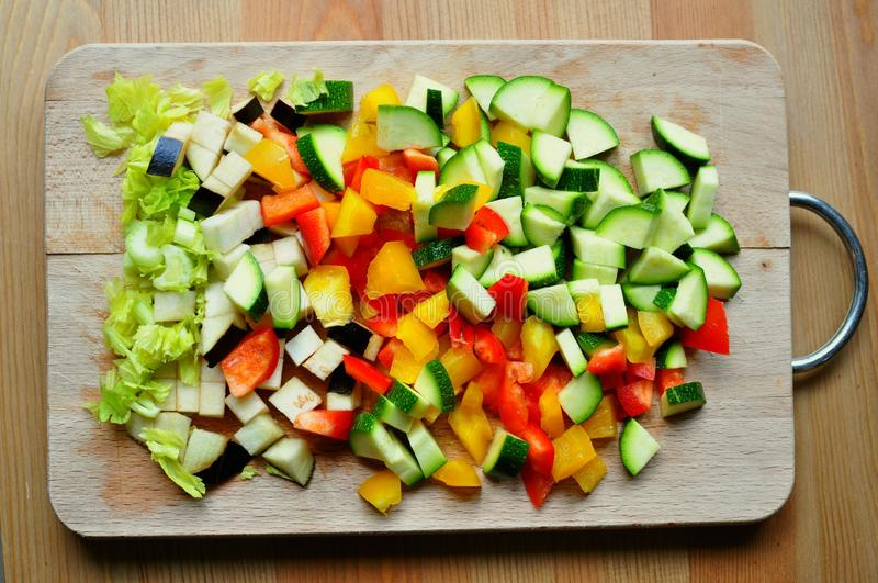Home cooking from scratch concept with vegetables on a wooden board. Cooking a meal from scratch concept : vegetables cut into small pieces ready to be cooked stock photo