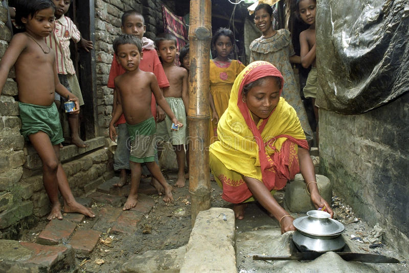 Cooking in shabby alley slum Mirpur, Bangladesh. Bangladeshi, capital, city Dhaka: in the slum Mirpur is a woman preparing food, meal, under great interest of a royalty free stock image