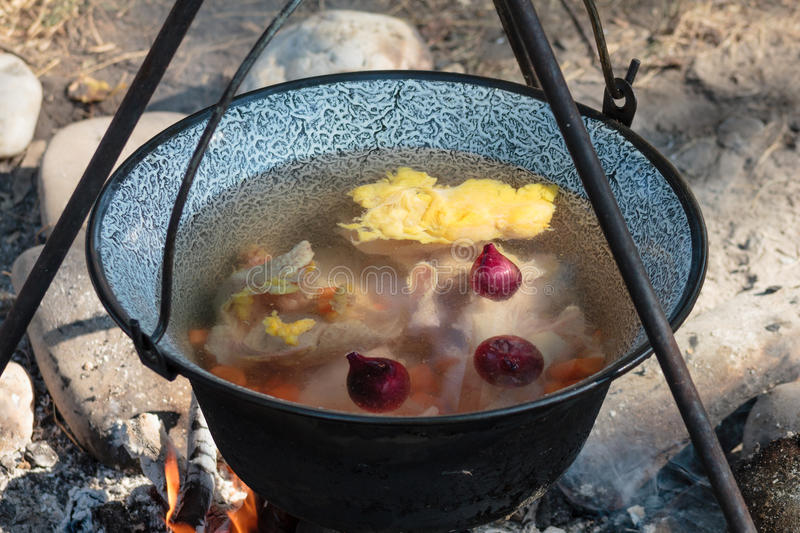 Cooking soup in a kettle on an open fire stock images