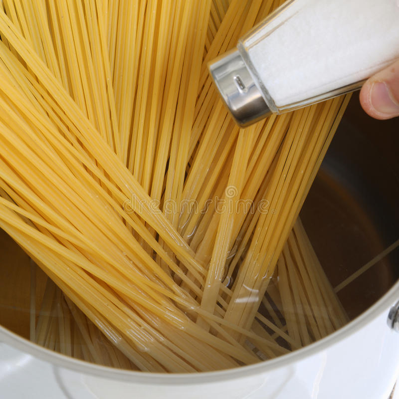 Cooking spaghetti noodles pasta meal salting water in the pot royalty free stock photo