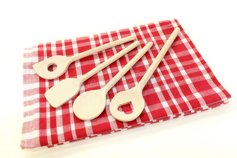 Cooking spoon on a napkin. Liight wooden cooking spoon on a checkered napkin stock photo